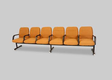 Row of 6 orange school auditorium chairs